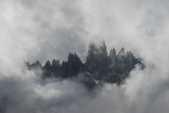 Close up of dark alpine peaks framed by stormy clouds