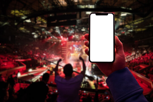 Gamer using smartphone during big esports gaming event sitting on the tribunes inside the arena. Blank screen with copy space mockup