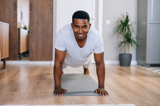 Front view of cheerful African-American man doing push-up on floor at bright domestic room, looking at camera. Concept of sport workout training at home gym.