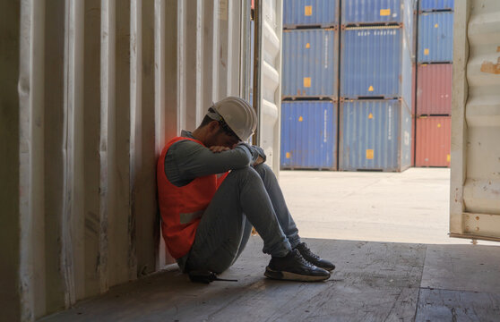 A fired man. Stressed upset depressed worried disappointed worker working in cargo container warehouse industry factory site in export, import, and transportation concept. Business people.