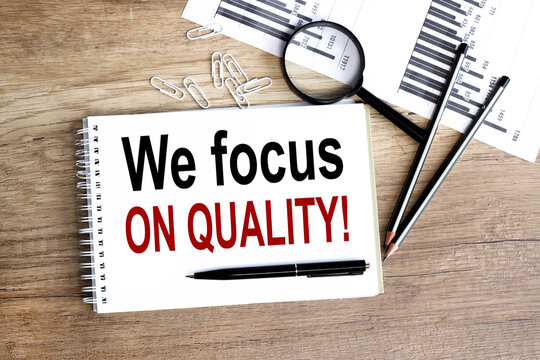 we focus on quality, text on white notepad paper on wood background, near a magnifying glass.
