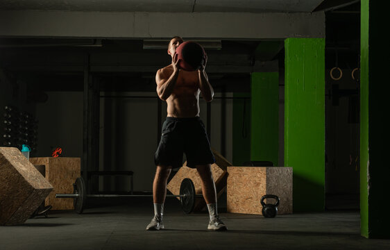 Fit man throwing medicine ball doing ball slam against gym floor or shoulder press exercise..