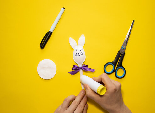 Making Easter bunny from plastic spoon and cotton pad on yellow background. Homemade easy children's craft. Simple creative art project.Step by step instructions.Decor for spring. DIY concept. Step 7