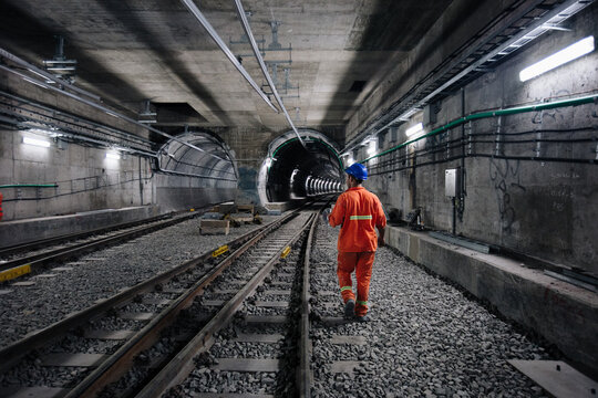 worker walking at railway tunnel