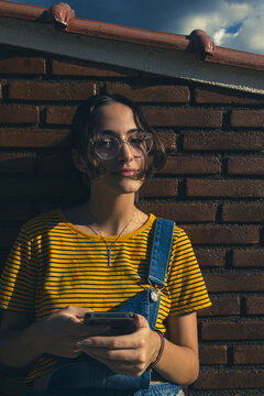 Teenager girl wearing colorful clothes and transparent clear eyeglasses in front of a red brown brick wall holding her smartphone. Downtown city centre autumn concept.