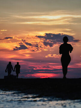 Silueta a contraluz de una mujer corriendo por la orilla de la playa al atardecer y una pareja de novios al fondo cogidos de la mano