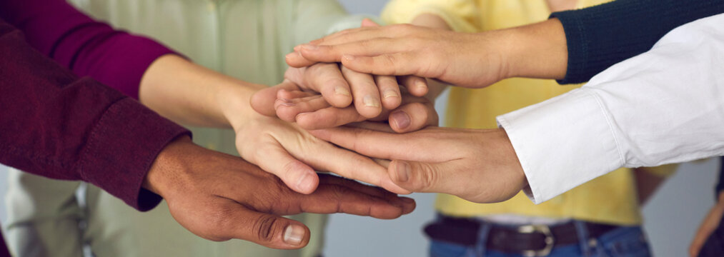 Close up of a group of international people folding their arms, supporting each other. People fold their arms as a sign of teamwork. Concept of unity, joint efforts, participation and bonding.