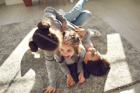Happy family enjoying quality time at home. Mom and little children frolicking on carpet. Cheerful mother and funny carefree kids playing, laughing and having fun on floor rug in sunny living-room