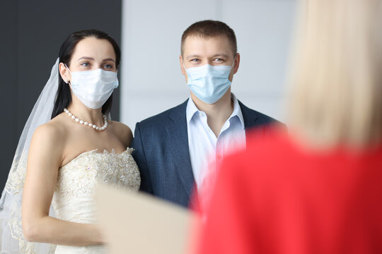 Man and woman in wedding suits and medical protective masks at ceremony