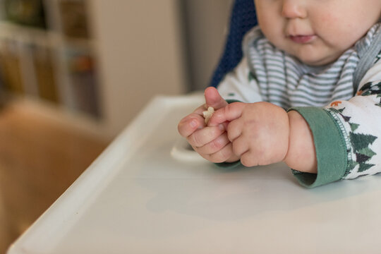7 month old baby learning pincer grasp to eat small puff cereal; two hands grasp food baby led weaning