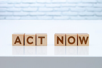 'Act Now' message sign on wooden blocks sitting on a white table with white brinks on the background.