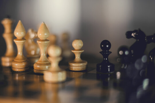 Wooden chess pieces on the chessboard.
