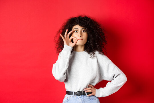 Image of cute girl with curly hair making promise to stay quiet, zipping lips, making seal, hiding a secret, standing dumb on red background