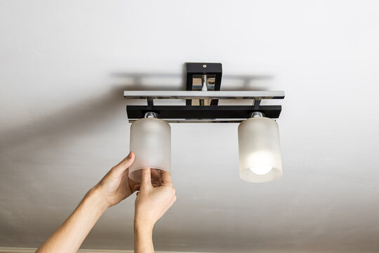 handyman replacing light bulb at wall lamp. changing light equipment for more energy efficient concept. electricity save conceptual
