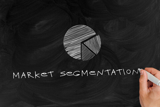 a man writes with a marker on a chalk board the words market segmentation next to the diagram