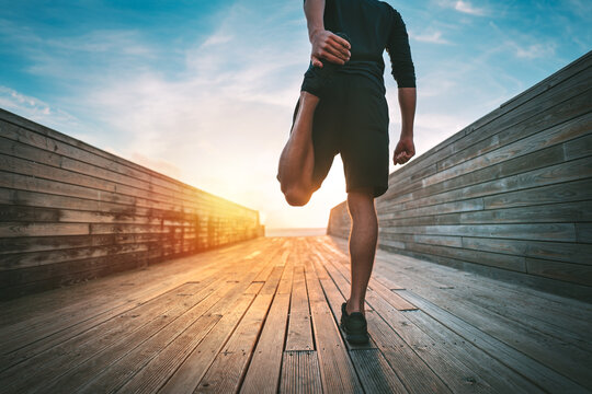 Young slim sporty man warming and stretching legs before run outdoors at sunset or sunrise. Athletic man in black sportswear doing fitness stretching exercises. Sport and healthy lifestyle.