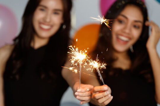 Two young and beautiful sexy Asian girls in a black dress playing with small little fireworks with fun and happiness in celebrating party