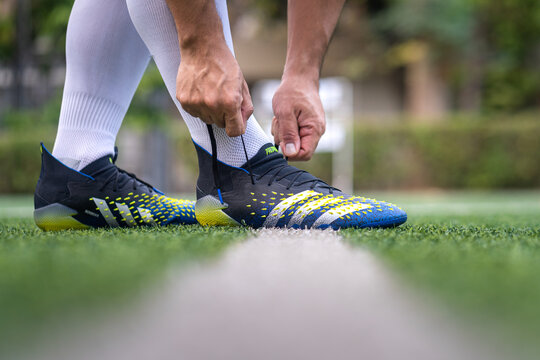 """Bangkok, Thailand - January 2021 : A football player is wearing adidas """"Predator Freak"""" which is design for striker feature on turf training ground. Close-up and selective focus, sport action photo."""
