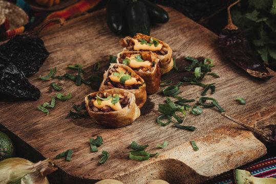 Bodegón de una deliciosa comida mexicana con chiles y vegetales al rededor en una tabla de madera