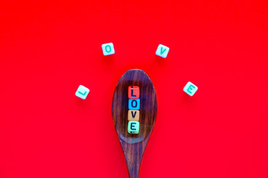 Directly Above Shot Of Alphabet Beads On Wooden Spoon Against Red Background