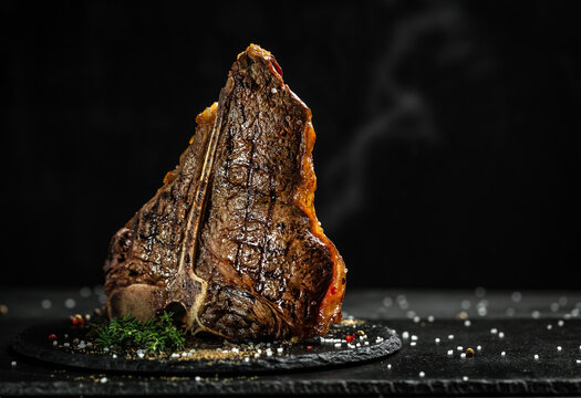 Grilled T-bone steak on stone table. juicy steak rare beef with spices on a black table, banner, menu, recipe, place for text