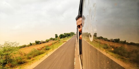 Cropped Portrait Of Man Looking Through Vehicle Window On Road Against Sky