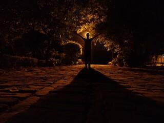 Fototapeta Silhouette Man Standing On Footpath At Night