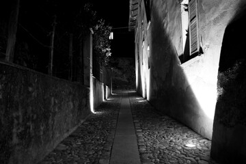 Narrow Alley Amidst Buildings In City At Night