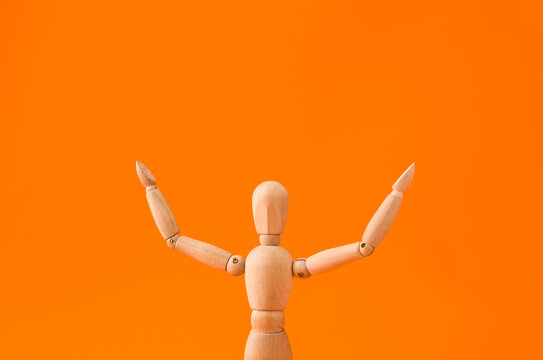 Wooden mannequin raising hands on color background
