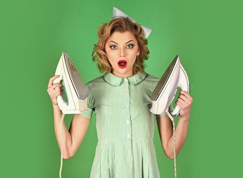 Young beautiful vintage housewife ironing on green background. Woman with iron.
