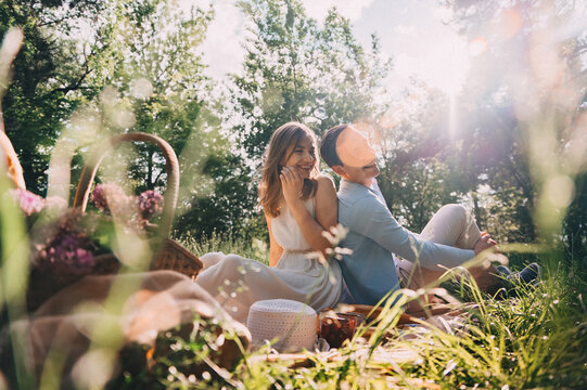 Lovely couple in love organized a picnic in the park wicker basket with flowers and food on the bedspread. happy lovers laugh and eat at the picnic. romantic date