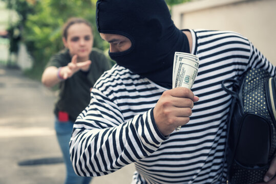 Close-up Of Thief Holding Money While Woman Chasing Outdoors