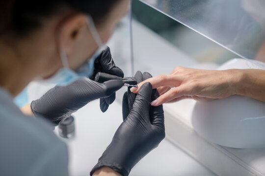 Nail artist working with the client in a beauty salon