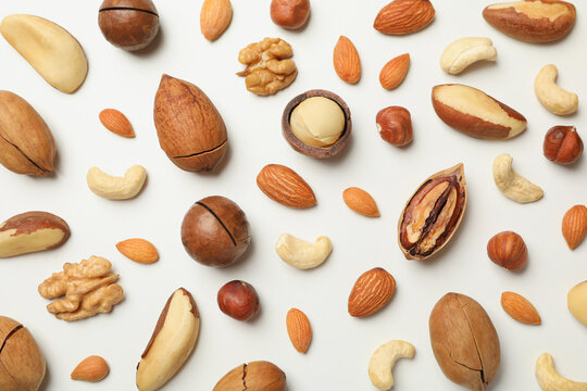Different tasty nuts on whole background, close up
