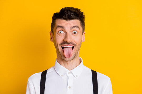 Photo portrait of funny comic student fooling grimacing showing tongue staring isolated on bright yellow color background