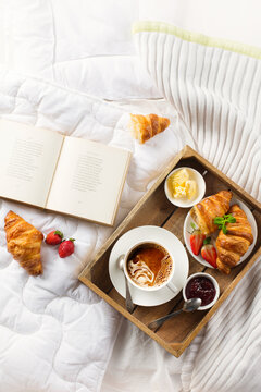 Morning breakfast in bed with coffee, fresh croissants, jam, fresh strawberries.