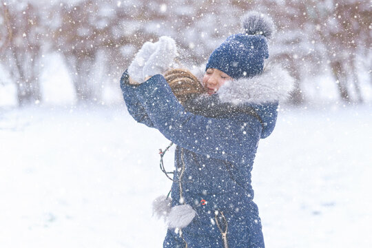 child girl playing with snow in winter outdoor and having fun on snowy winter