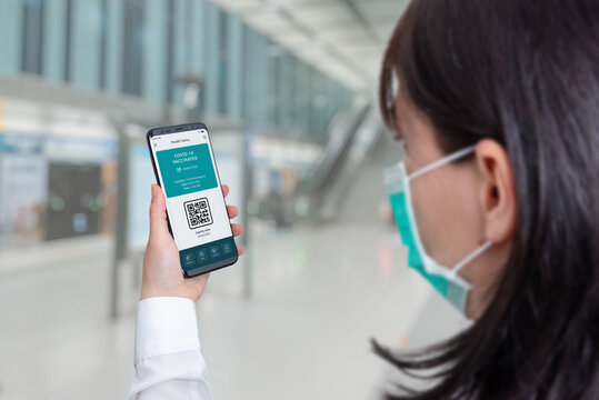 Covid-19 health pass app concept on smart phone. Woman hodling phone on airport departures