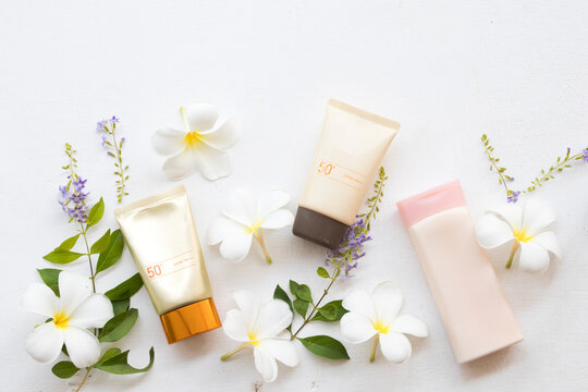 natural cosmetics sunscreen spf50 two pieces health care skin face and body lotion of lifestyle woman relax summer with flower frangipani arrangement flat lay style  on background white