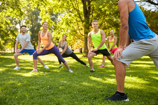 fitness, sport and healthy lifestyle concept - group of happy people exercising with trainer at summer park