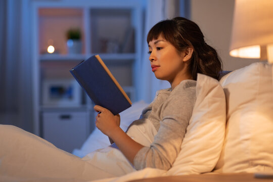 people, bedtime and rest concept - young asian woman reading book in bed at home at night