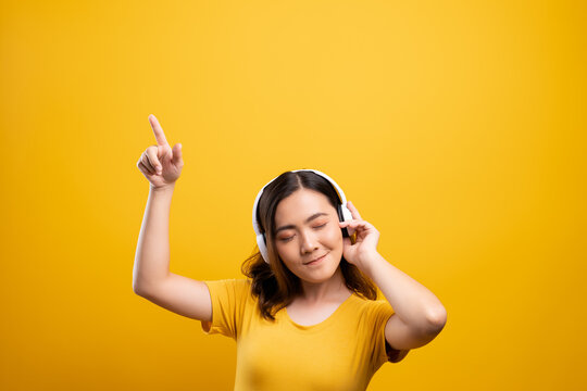 Smiling Young Woman Wearing Headphones Against Yellow Background