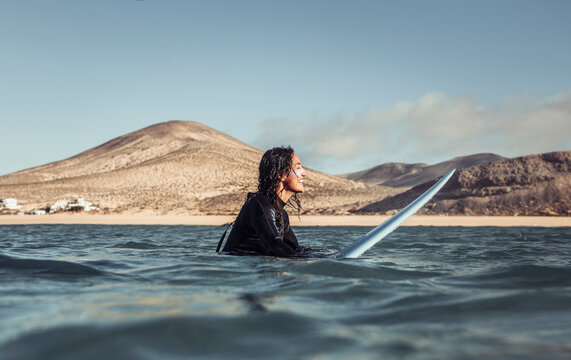 Woman surfing in the sea with a yellow surfboard