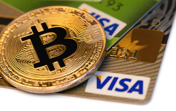 bitcoin cryptocurrency with Visa credit card closeup, macro. Visa - American multinational company providing services of payment operations. Moscow, Russia - August 17, 2020