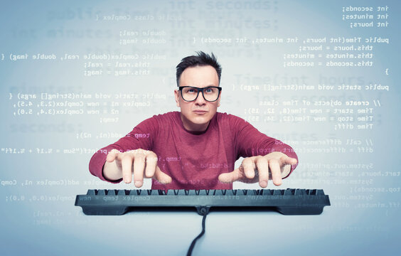 Portrait of a man in glasses and a red T-shirt who types on the keyboard and looks at the monitor with computer code. Front view.