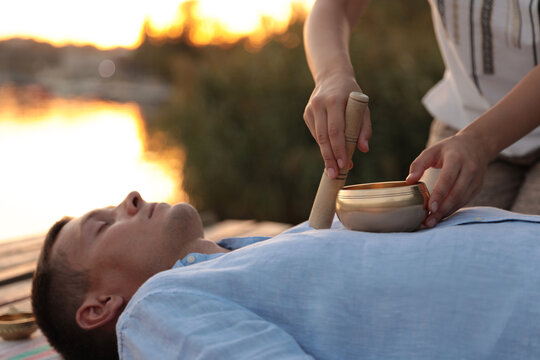 Man at healing session with singing bowl outdoors