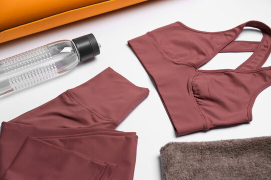 Stylish sportswear, bottle of water and yoga mat on white background