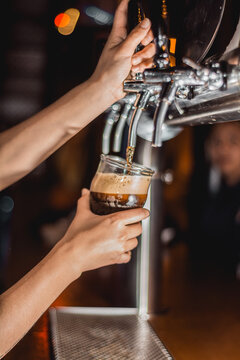 bartender pouring beer in bar