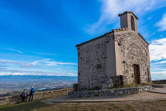 Tourists enjoying the breathtaking view on the Rhone valley and Valence city from high lookout of the belvèdere du pic of the french Saint-Romain-de-Lerps village with the tiny chapel behind.