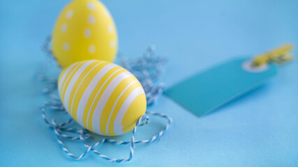 Easter painted colorful decorated yellow eggs on blue background. Minimal easter concept.